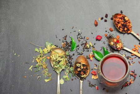 Stilleven, eten en drinken concept. Verschillende soorten thee met een glas thee op een zwart bord. Selectieve aandacht, kopie ruimte achtergrond, bovenaanzicht. Stockfoto