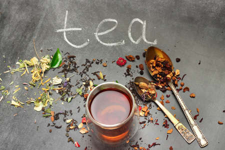 mint tea: Still life, food and drink concept. Various kinds of tea with a glass of tea on a black chalkboard. Selective focus, copy space background, top view.