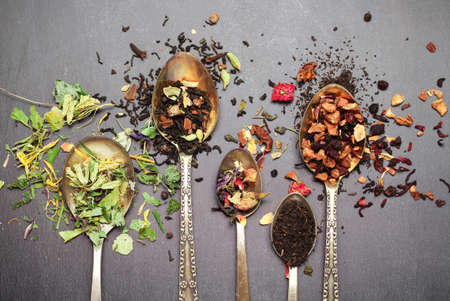 herbal background: Still life, food and drink concept. Various kinds of tea in a spoon on a black chalkboard. Selective focus, copy space background, top view Stock Photo