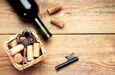 spirit: Still life, food and drink, holidays concept. Basket with wine corks, bottle and corkscrew on a wooden table. Selective focus, copy space background, top view