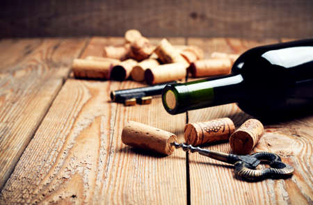Still life, food and drink, holidays concept. Wine corks, bottle and corkscrew on a wooden table. Selective focus, copy space background