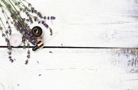 Still life, health and beauty, spa concept. Dry lavender and oil  on a white wooden table. Selective focus, copy space background, top view