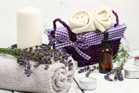white towels: Still life, health and beauty, spa concept. Dry lavender and oil  on a white wooden table. Selective focus