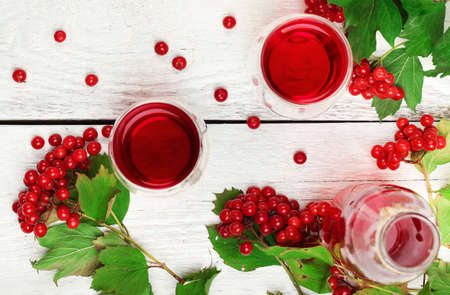 guelder rose: Still life, food and drink, health and homeopathy concept. Viburnum (guelder rose) drink in glass on a wooden table. Selective focus, top view