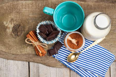 leche: Naturaleza muerta, comida y bebida, navidad y vacaciones concepto. Ingredientes para el cacao casera (cacao en polvo, leche, chokolate, canela) en una mesa de madera. Enfoque selectivo, espacio de copia, vista superior