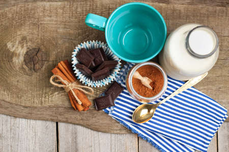 mleko: Still life, food and drink, christmas and holidays concept. Ingredients for homemade cacao (cocoa powder, milk, chokolate, cinnamon) on a wooden table. Selective focus, copy space, top view Zdjęcie Seryjne