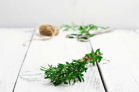 Still life, food and drink, health concept. Fresh herbs (savory) on a wooden table. Selective focus, copy space white background, rustic style