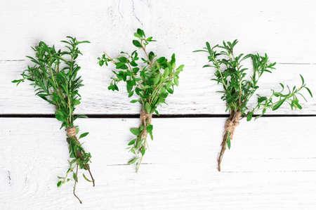 Nature morte, de la nourriture et la boisson, le concept de la santé. Mélanger des herbes fraîches sur une table en bois, la sarriette et le thym. mise au point sélective, vue de dessus
