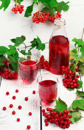 guelder rose: Still life, food and drink, health and homeopathy concept. Viburnum (guelder rose) drink in glass on a wooden table. Selective focus