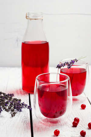 bebidas frias: Still life, food and drink, health and homeopathy concept. Cranberry (red berries) drink in glass with lavender on a wooden table. Selective focus Foto de archivo