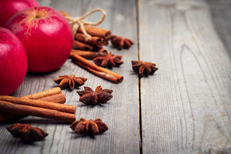 fall harvest: Still life, food and drink, seasonal concept. Autumn apples with spices (star anise and cinnamon sticks) on a wooden background. Selective focus, copy space