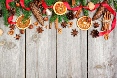 top of the year: Still life, food and drink, seasonal and holidays concept. Christmas decoration with fir tree, oranges, cones, nuts, spices on a wooden table. Selective focus, copy space background, top view