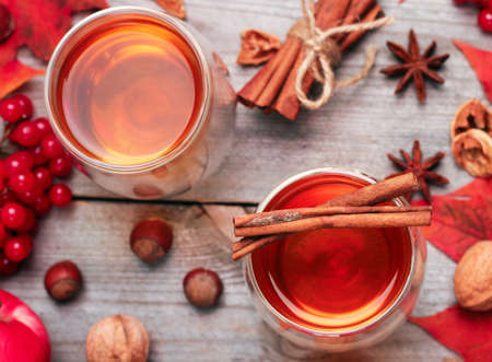 Still life, food and drink, seasonal and holidays concept. Autumn hot beverage in a glass with fruits and spices on a wooden background. Selective focus, top view Archivio Fotografico