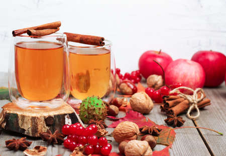 flavours: Still life, food and drink, seasonal and holidays concept. Autumn hot beverage in a glass with fruits and spices on a wooden background. Selective focus Stock Photo