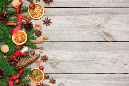Still life, food and drink, seasonal and holidays concept. Christmas decoration with fir tree, oranges, cones, nuts, spices on a wooden table. Selective focus, copy space background, top view