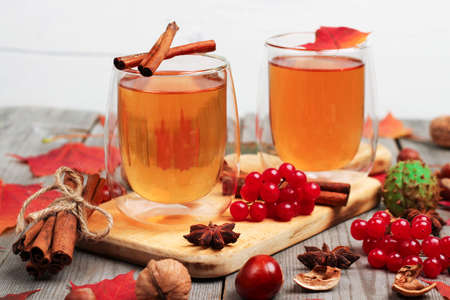 orange rose: Still life, food and drink, seasonal and holidays concept. Autumn hot beverage in a glass with fruits and spices on a wooden background. Selective focus Stock Photo