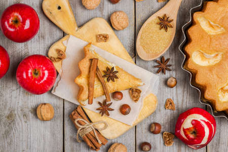 Still life, food and drink, seasonal concept. Apple pie nuts and spices (cinnamon and star anise) on a rustic wooden table. Selective focus, top view