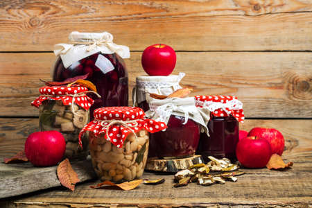 dried food: Still life, food and drink, seasonal concept. Autumn preserved fruits, vegetables and mushrooms on a rustic wooden table. Selective focus, copy space background