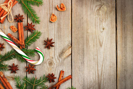 azucar: Still life, seasonal and holidays concept. Christmas decoration with fir tree, sugar cane and spices (cinnamon, anise star) on a wooden table. Selective focus, copy space, top view