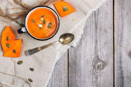 Still life, food and drink, seasonal concept. Fresh orange pumpkin soup in a mug on a rustic wooden table. Selective focus, copy space, top view Archivio Fotografico