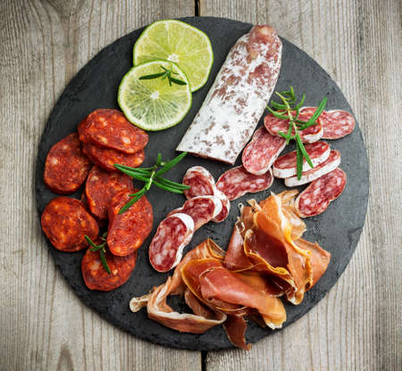 Still life, food and drink, holidays concept. Assortment of spanish tapas or italian antipasti, jamon, prosciutto, chorizo, salami on a grunge black board, rustic style. Selective focus, top view
