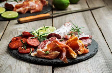 spanish tapas: Todav�a vida, comida y bebida, el concepto de vacaciones. Surtido de tapas espa�olas o antipasti italiano, jam�n, jam�n, chorizo, salami en un tablero negro del grunge, estilo r�stico. enfoque selectivo