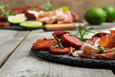 spanish tapas: Still life, food and drink, holidays concept. Assortment of spanish tapas or italian antipasti, jamon, prosciutto, chorizo, salami on a grunge black board, rustic style. Selective focus
