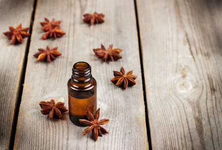 bath supplement: Still life, food and drink, healthcare, beauty concept. Organic anise essential oil on a rustic wooden table. Selective focus