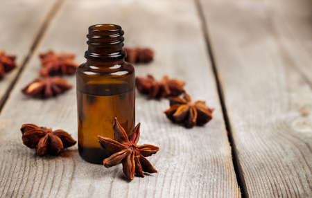 bath supplement: Still life, food and drink, healthcare, beauty concept. Organic anise essential oil on a rustic wooden table. Selective focus, copy space background