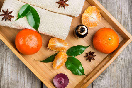bath supplement: Still life, healthcare, beauty concept. Spa assortment with organic tangerine essential oil in a tray on a rustic wooden table. Selective focus, top view