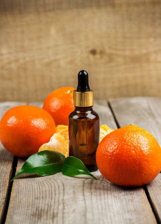 bath supplement: Still life, food and drink, healthcare, beauty concept. Organic tangerine essential oil on a rustic wooden table. Selective focus
