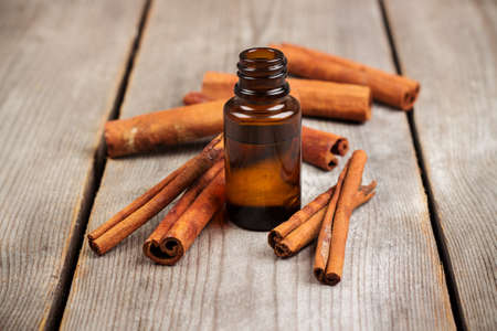 bath supplement: Still life, food and drink, healthcare, beauty concept. Organic cinnamon essential oil on a rustic wooden table. Selective focus