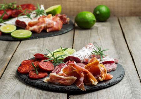 food still: Still life, food and drink, holidays concept. Assortment of spanish tapas or italian antipasti, jamon, prosciutto, chorizo, salami on a grunge black board, rustic style. Selective focus
