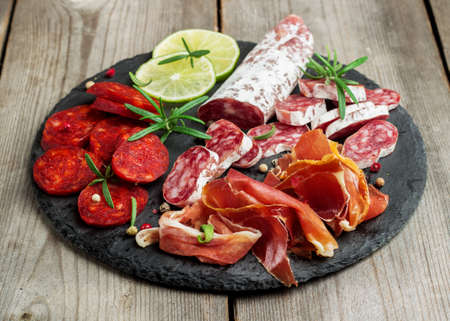 Still life, food and drink, holidays concept. Assortment of spanish tapas or italian antipasti, jamon, prosciutto, chorizo, salami on a grunge black board, rustic style. Selective focus