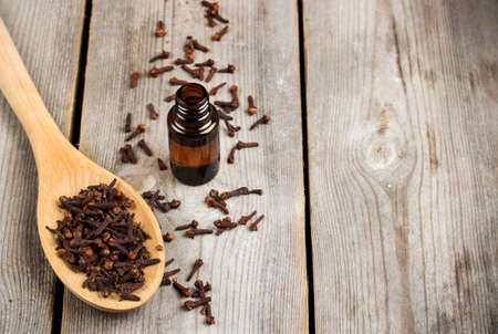 Organic clove essential oil on a rustic wooden table. Selective focus, copy space background