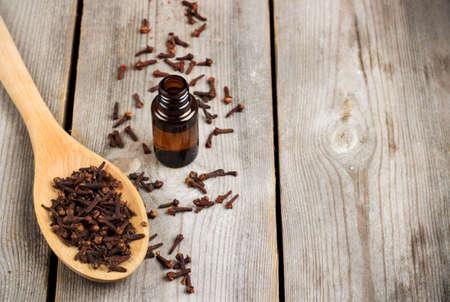 Organische Nelke ätherisches Öl auf einem rustikalen Holztisch. Selektiver Fokus, Kopie Raum Hintergrund