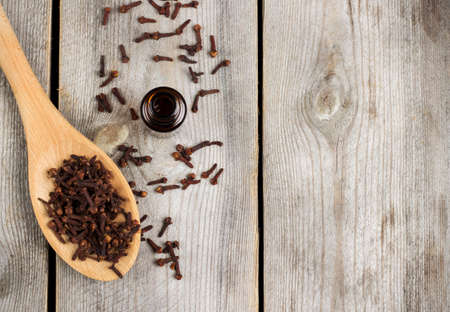 bath supplement: Still life, food and drink, healthcare, beauty concept. Organic clove essential oil on a rustic wooden table. Selective focus, copy space background Stock Photo