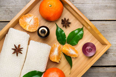 bath supplement: Spa assortment with organic tangerine essential oil in a tray on a rustic wooden table. Selective focus, top view