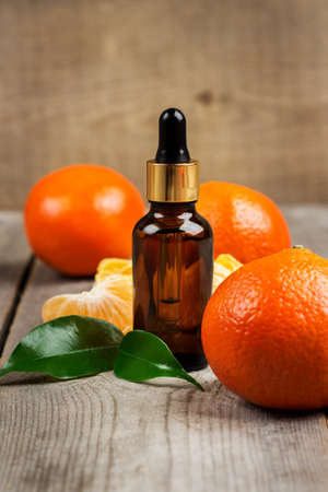 bath supplement: Organic tangerine essential oil on a rustic wooden table. Selective focus