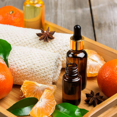 bath supplement: Spa assortment with organic tangerine essential oil in a tray on a rustic wooden table. Selective focus Stock Photo