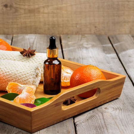 bath supplement: Still life, healthcare, beauty concept. Spa assortment with organic tangerine essential oil in a tray on a rustic wooden table. Selective focus Stock Photo