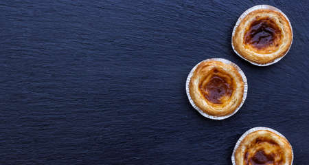 nata: Egg tart on a grunge background, traditional portugueser dessert, pasteis de nata. Selective focus, flat lay, copy space
