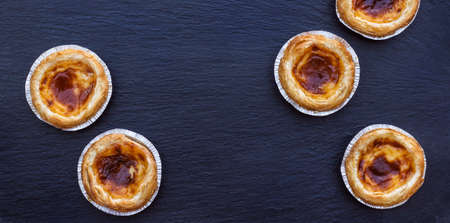 nata: Egg tart on a grunge background, traditional portuguese dessert, pasteis de nata. Selective focus, flat lay