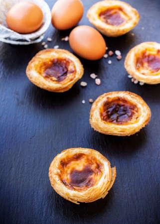 nata: Egg tart on a grunge background, traditional portuguese dessert, pasteis de nata. Selective focus Stock Photo