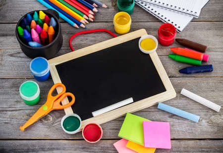 Education and business concept. School supplies with crayons, paint, chalk and copy space chalkboard on a wooden background. Selective focus, top view Standard-Bild