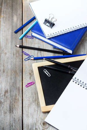 assortment: Still life, business, education concept. Assortment of office and school supplies and chalkboard on a rustic wooden table. Selective focus, copy space background, top view