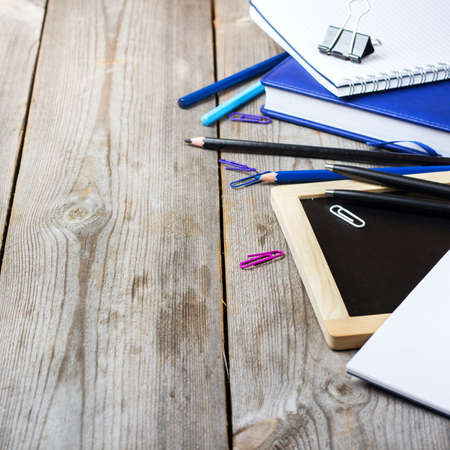 assortment: Still life, business, education concept. Assortment of office and school supplies and chalkboard on a rustic wooden table. Selective focus, copy space background Stock Photo