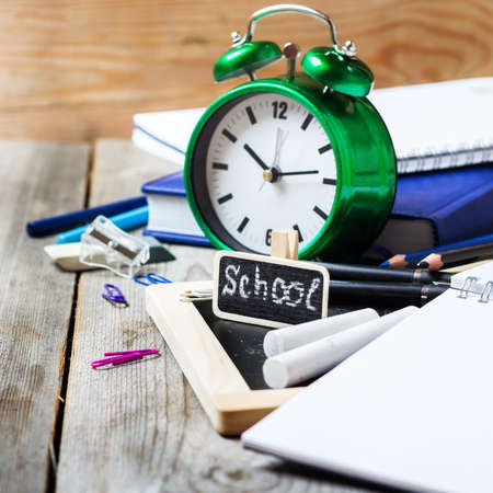assortment: Still life, business, education concept. Assortment of office and school supplies, alarm clock and chalkboard on a rustic wooden table. Selective focus, copy space background