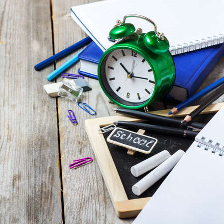 assortment: Still life, business, education concept. Assortment of office and school supplies, stationery, alarm clock and chalkboard on a rustic wooden table. Selective focus