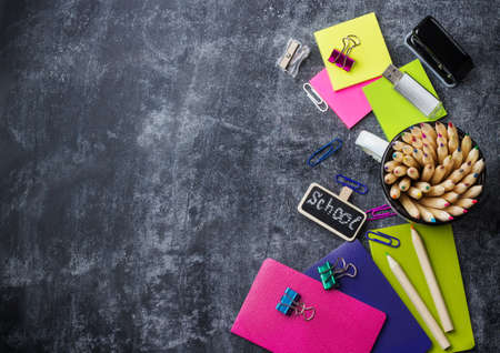 Education, back to school concept. School stationery, supplies, pencil, pen, note on a grunge chalkboard. Selective focus, copy space background, flat lay, top view Archivio Fotografico